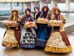 Дівчата в старовинних сукнях продають цукерки